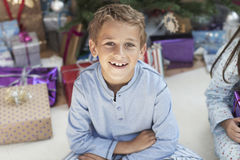 Happy Young Boy With Christmas Presents. Portrait of happy young boy with Christmas presents at home Royalty Free Stock Photos