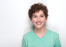 Happy young boy with curly hair smiling. Close up portrait of a happy young boy with curly hair smiling against white background Stock Photo