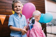 Happy young boy and little girl at birthday party. Happy young boy and cute little girl at birthday party Royalty Free Stock Photos