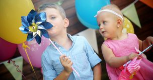 Happy young boy and little girl at birthday party. Happy young boy and cute little girl at birthday party Stock Photos