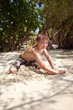 Happy young boy is digging at the beach Stock Image