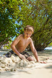 Happy young boy is digging in the sand of the beach and construc Stock Image