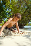 Happy young boy is digging in the sand of the beach and construc Royalty Free Stock Images