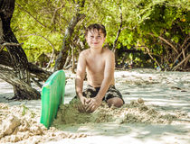 Happy young boy is digging in the sand of the beach Royalty Free Stock Images