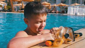 Happy young boy in diving mask relaxing in blue water pool at the hotel of Egypt stock video