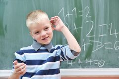 Happy young boy at first grade math classes. Solving problems and finding solutions Stock Photo
