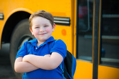 Happy young boy in front of school bus royalty free stock image
