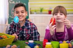 Happy young boy and girl playing with Easter eggs Stock Photo