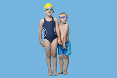 Happy young boy and girl in swimwear holding hands over blue background Stock Image