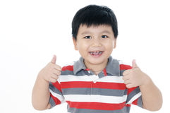 Happy young boy giving thumbs up sign. Portrait of a happy young boy giving thumbs up sign on white background Royalty Free Stock Photography