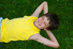 Happy young boy on grass. A happy young boy resting on his back on grass royalty free stock image