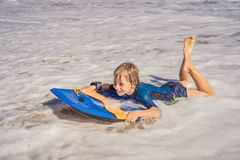 Happy Young boy having fun at the beach on vacation, with Boogie board.  royalty free stock images