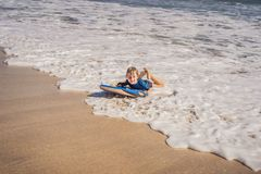 Happy Young boy having fun at the beach on vacation, with Boogie board.  stock photo