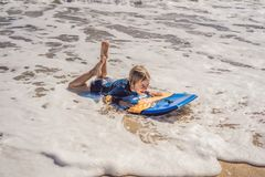 Happy Young boy having fun at the beach on vacation, with Boogie board.  royalty free stock photos