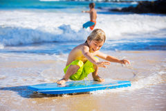 Happy Young boy having fun at the beach on vacation. With boogie board Royalty Free Stock Photos