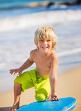 Happy Young boy having fun at the beach on vacation,. With boogie board Stock Image