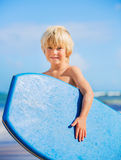 Happy Young boy having fun at the beach on vacation,. With boogie board Royalty Free Stock Photo