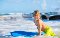Happy Young boy having fun at the beach on vacation. With boogie board Stock Photo