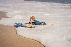 Happy Young boy having fun at the beach on vacation, with Boogie board.  stock image