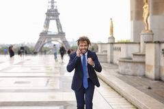 Jocund mulatto guy raving near Eiffel Tower and calling friend b. Happy young boy having fun and talking with friend with smartphone near Eiffel Tower in Stock Images