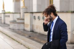 Jocund mulatto guy raving near Eiffel Tower and calling friend b. Happy young boy having fun and talking with friend with smartphone near Eiffel Tower in Stock Image