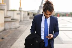 Jocund mulatto guy raving near Eiffel Tower and calling friend b. Happy young boy having fun and talking with friend with smartphone near Eiffel Tower in Royalty Free Stock Photos