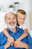 Happy young boy with his grandfather. Standing behind him with his arms around his neck in a loving embrace Royalty Free Stock Images