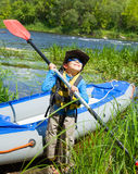 Happy young boy holding paddle near a kayak Stock Images