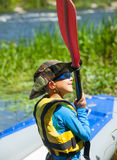Happy young boy holding paddle near a kayak Stock Image