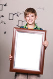 Happy young boy holding portrait frame Royalty Free Stock Image