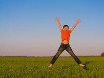 Happy young boy jumping outdoors with raised arms. Stock Images