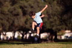 Happy young boy jumping and playing in the park. Copy space left and right Royalty Free Stock Photography