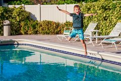 Happy young boy jumping to the pool water in golden hours time royalty free stock image