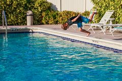 Happy young boy jumping to the pool water in golden hours time stock images