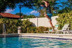Happy young boy jumping to the pool water in golden hours time stock photography