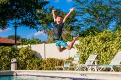 Happy young boy jumping to the pool water in golden hours time stock photos