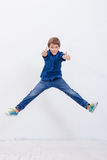 Happy young boy jumping  on white background. Happy young boy jumping over a white background Stock Image