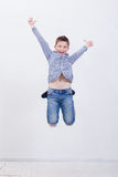 Happy young boy jumping  on white background. Happy young boy jumping over a white background Royalty Free Stock Photo