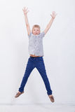 Happy young boy jumping  on white background. Happy young boy jumping over a white background Royalty Free Stock Images