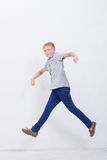 Happy young boy jumping  on white background. Happy young boy jumping over a white background Royalty Free Stock Photography