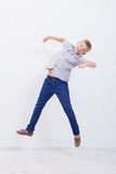 Happy young boy jumping  on white background. Happy young boy jumping over a white background Royalty Free Stock Photos