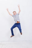 Happy young boy jumping  on white background. Happy young boy jumping over a white background Stock Photos