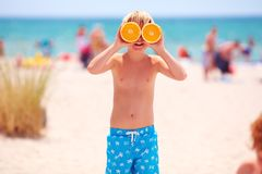 Happy young boy, kid with citrus eyes on sandy beach during summer vacation royalty free stock images