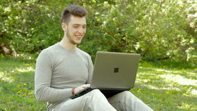 Happy young boy laughing and working with laptop stock footage