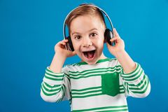 So happy young boy listening music by headphone. And looking at the camera with open mouth over blue background Stock Image