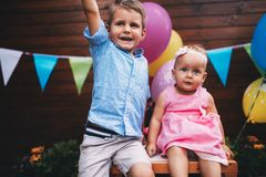 Happy young boy and little girl at birthday party Royalty Free Stock Image