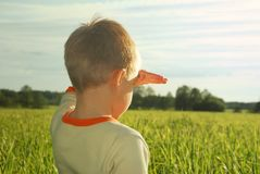 Happy young boy looking horizon and dreaming. On green field grass Stock Image
