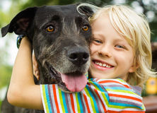 Happy young boy lovingly hugging his pet dog. In the park Stock Photo