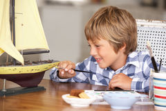 Happy young boy making model ship Royalty Free Stock Photos