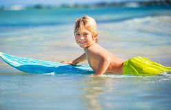 Happy young boy in the ocean on surfboard Royalty Free Stock Images